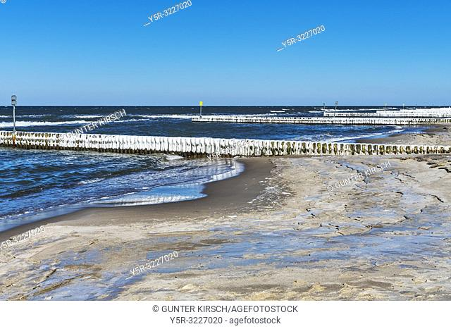 Beach of the Baltic Sea at Kolberg in winter.   Ice covered Groynes are in the water. Groynes are intended to break the shaft and to prevent the erosion of the...