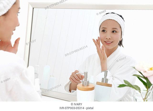 A young woman applying face cream