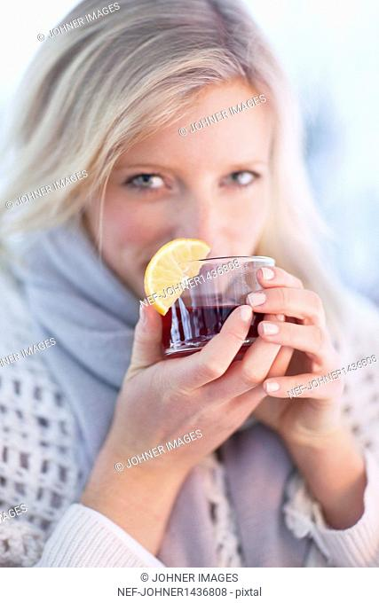 Woman drinking tea with lemon wedge indoors