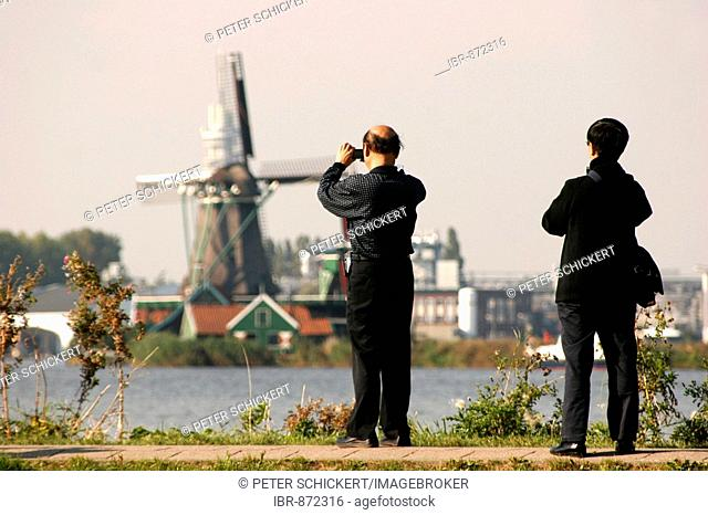 Japanese tourists take photos of a windmill in the Museum Zaanse Schans, Zaandam, Netherlands, Europe