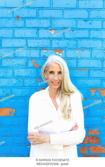 Portrait of smiling mature woman in front of light blue wall