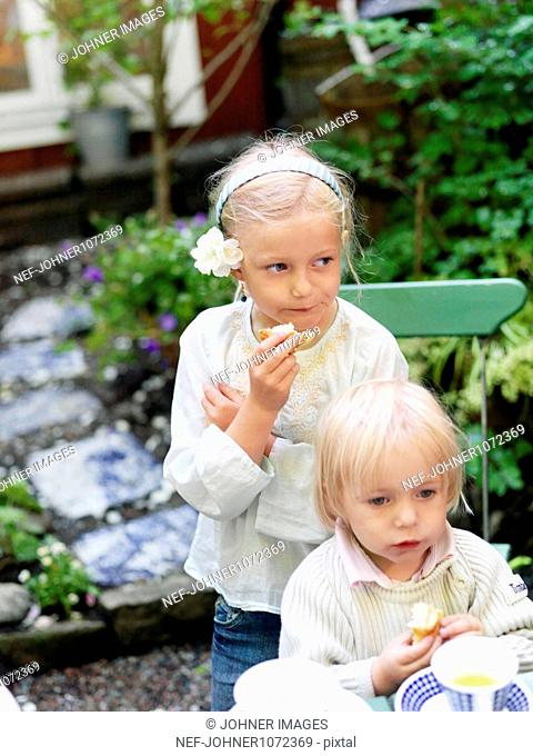 Girl and boy eating cakes