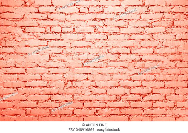 Coral color toned painted grunge vintage retro style brick wall background texture close up