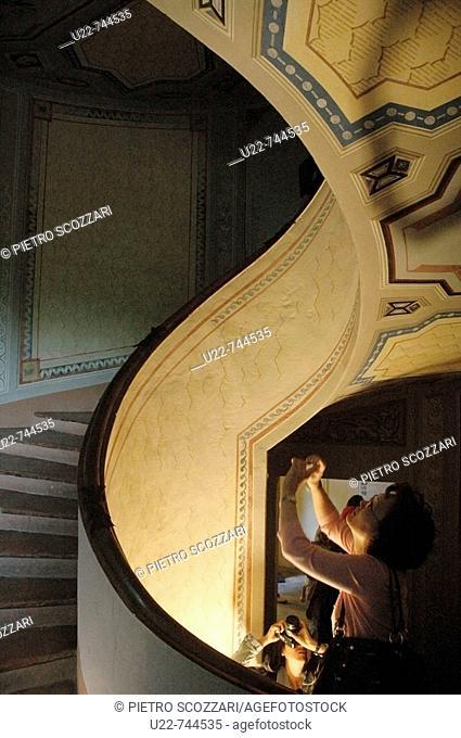 Vignola Modena, Italy, Asian tourists taking a photos at Palazzo Barozzi's winding staircase