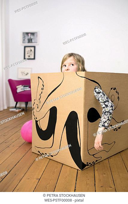 Girl inside a cardboard box painted with an octopus