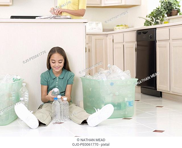 Young girl sitting on kitchen floor with empty plastic bottles and bin smiling