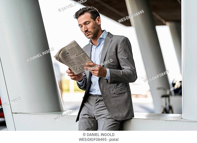 Portrait of businessman reading newspaper outdoors