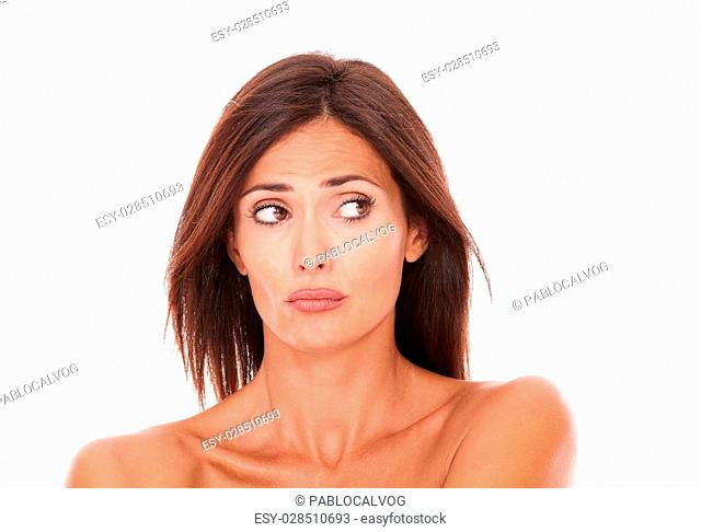 Headshot portrait of unsmiling latin woman with nude shoulders looking to her left on isolated white background - copyspace