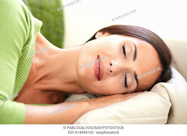 Attractive young woman resting horizontally with eyes closed - focus on foreground