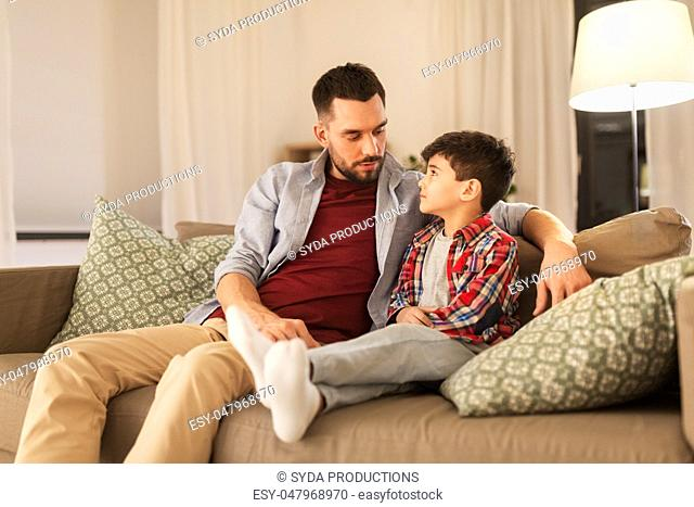 father talking to his sad little son at home