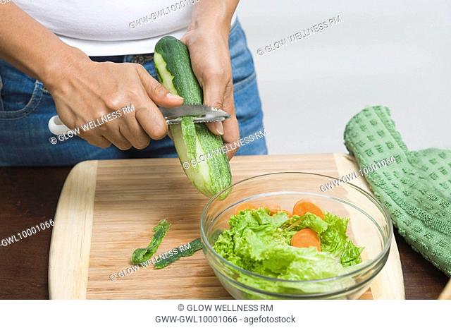 Mid section view of a woman peeling a cucumber