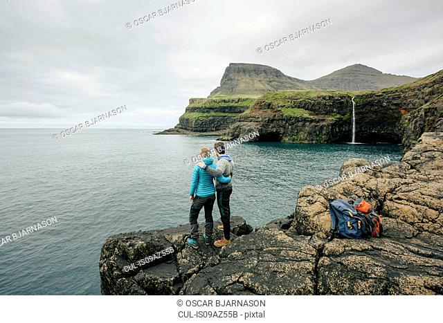 Hikers enjoying view from rocks, Gasadalur, Vagar, Faroe Islands