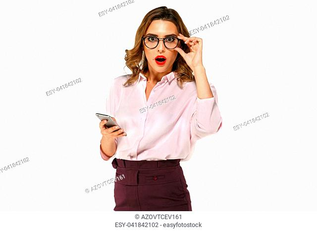 Attractive business woman looks surprised, holding mobile phone, dressed up in blouse and skirt, in eyeglasses, isolated on white background