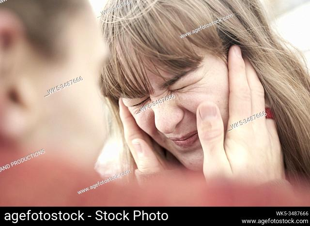 male hands holding face of troubled woman