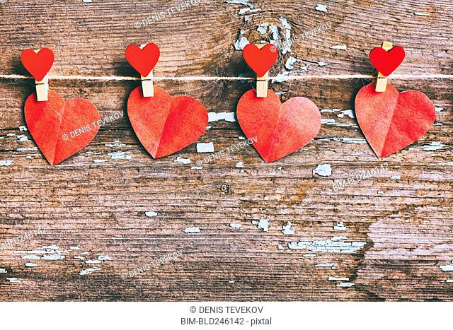Paper hearts hanging on string with clothespin