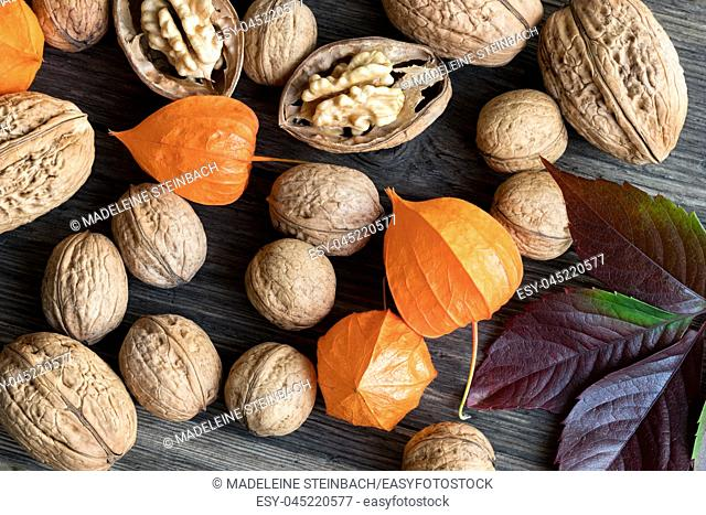 Whole and broken walnuts, Physalis (Chinese lantern) and autumn leaves on a wooden table, top view