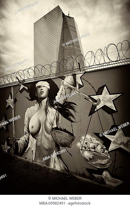 Euro-sceptic graffiti on site fence with barbed wire, half-blind (Lady) (Lady) Justice, new building of the European Central Bank, ECB, Ostend