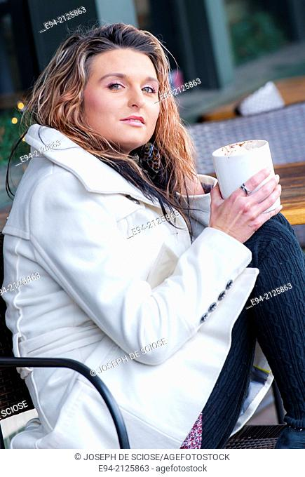 A 27 year old brunette woman sitting at an outdoor cafe and holding a white mug of hot chocolate looking at the camera