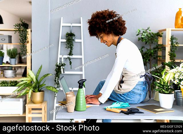 Female shop owner using laptop while sitting on table