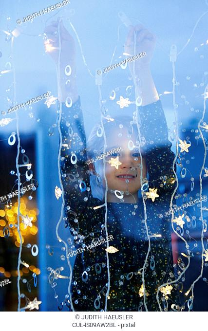 View through window of girl arms raised hanging decorative lights, looking at camera smiling