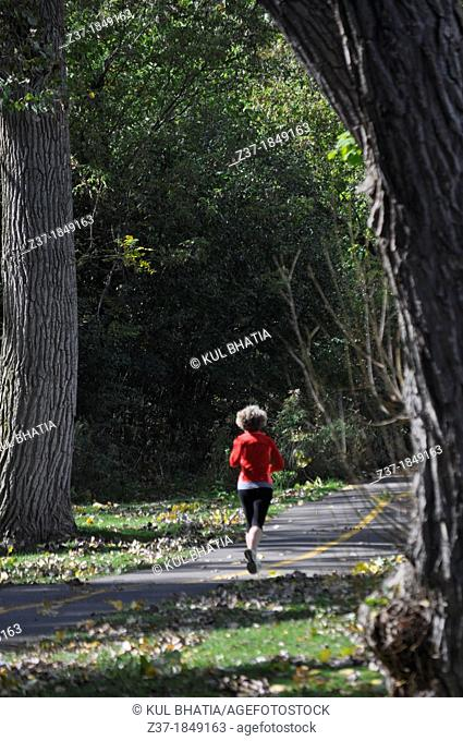 A lone woman jogs in a park on an autumn afternoon, Ontario, Canada