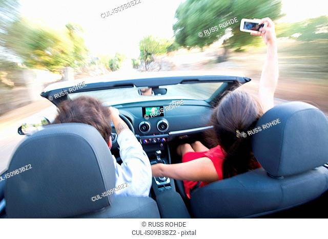 Rear view of young couple taking selfie whilst driving on rural road in convertible, Majorca, Spain