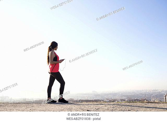 Female athlete listening to music with smartphone with cityscape in background