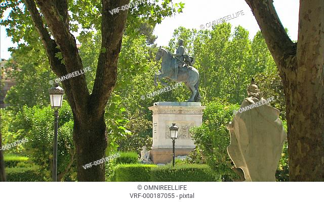 Statue King Felipe IV on horse surrounded by old lampposts and trees