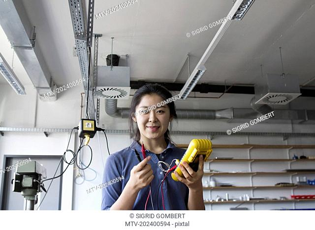 Young female engineer working with multimeter in an industrial plant, Freiburg Im Breisgau, Baden-württemberg, Germany
