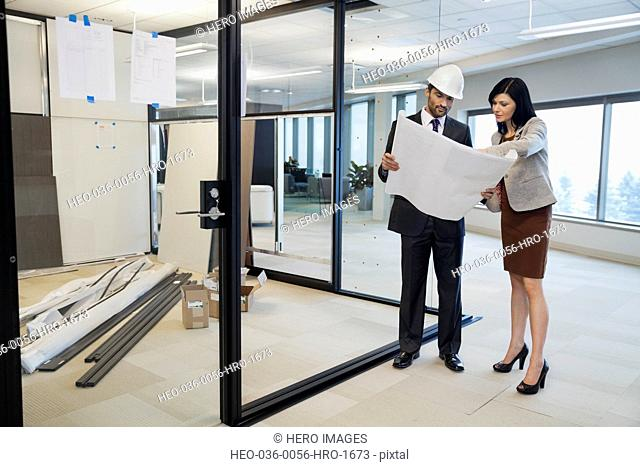 Architect and colleague examining blueprint at construction site
