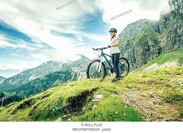 Germany, Bavaria, Pfronten, smiling teenage girl with mountain bike on alpine meadow near Aggenstein