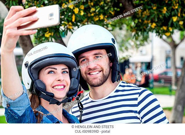 Young moped couple taking selfie in park, Split, Dalmatia, Croatia