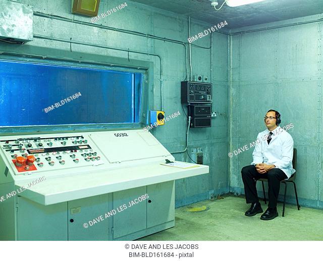 Caucasian scientist sitting in control room