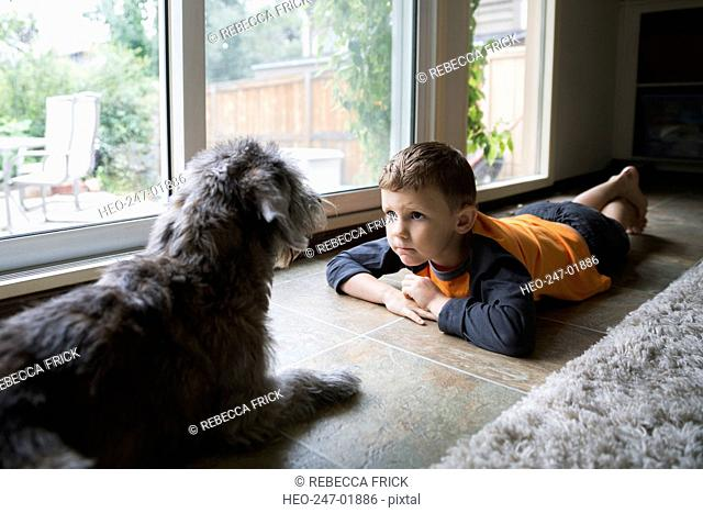 Serious boy staring at dog on floor