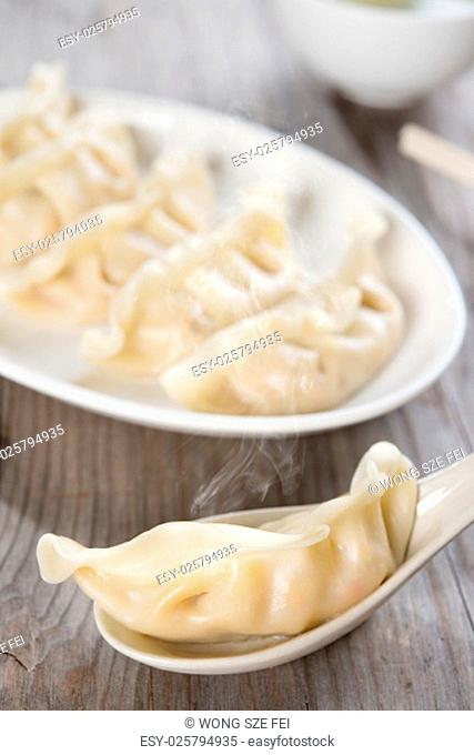 Fresh dumpling on spoon with hot steams. Chinese food on old wooden background