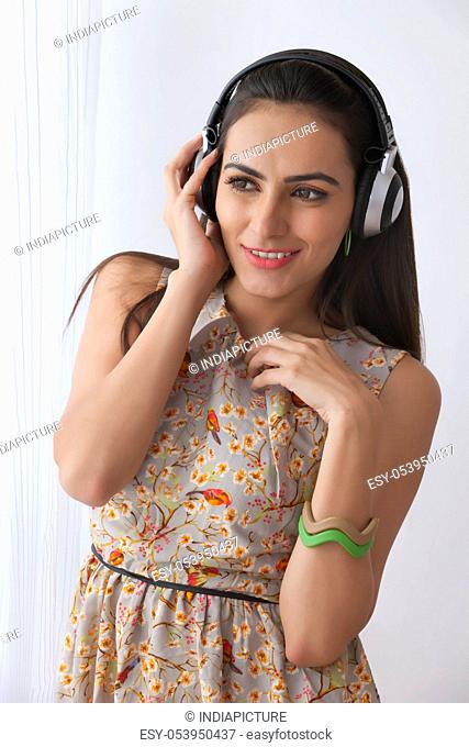 Beautiful young woman listening on headphones
