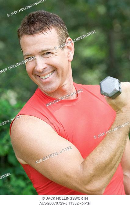 Portrait of a mature man exercising with a dumbbell