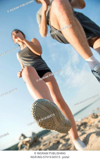 Legs View Of A Couple Jogging Outdoor on the Beach