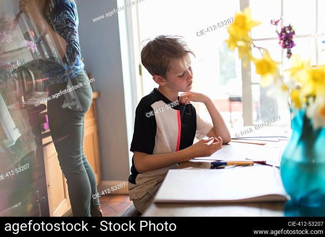 Boy doing homework at kitchen table