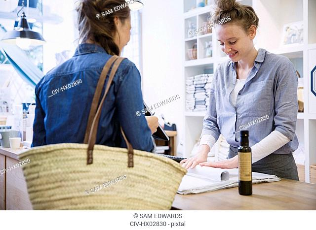Female cashier wrapping merchandise for shopper at checkout counter in shop