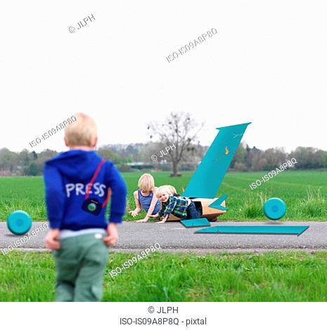 Children playing together in broken airplane model