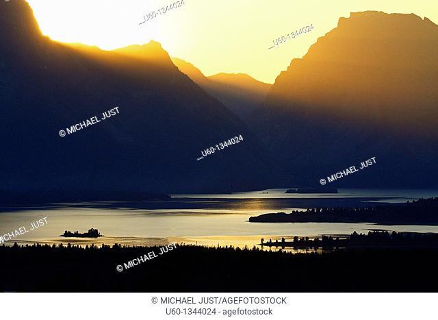 A setting sun shines over Jackson Lake and the Grand Tetons at Grand Teton National Park, Wyoming