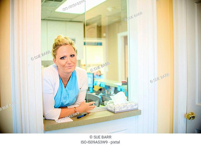 Portrait of female orthodontist at dentist reception hatch