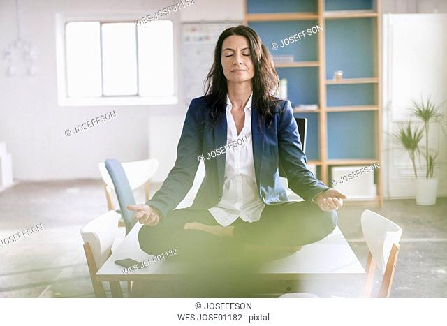 Businesswoman doing yoga exercise on desk in a loft