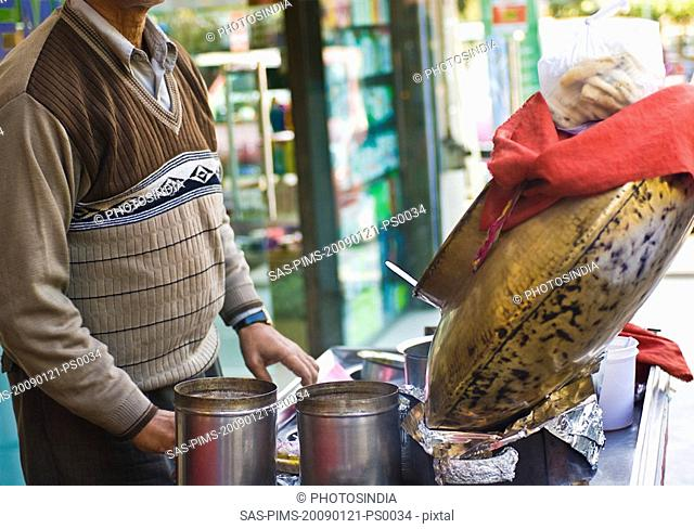 Mid section view of a man with food stall in a street market, New Delhi, India