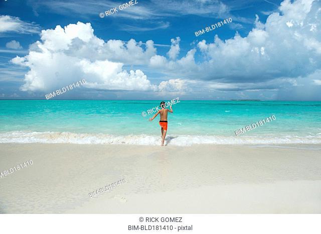 Hispanic boy running in waves on beach