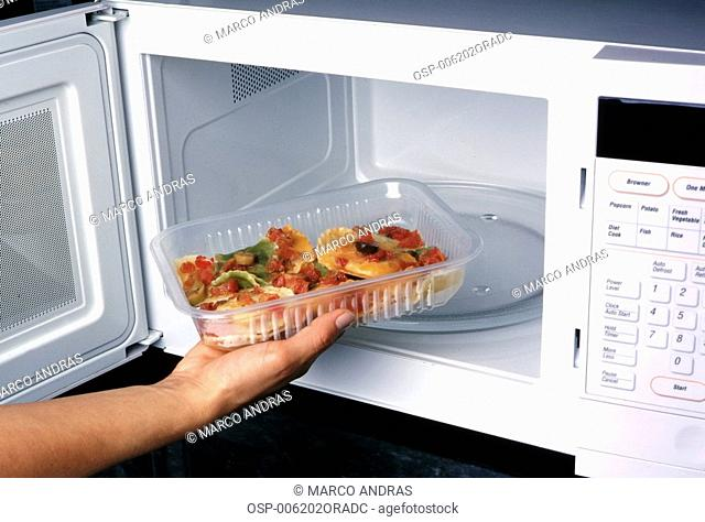 a person putting food inside the microwave