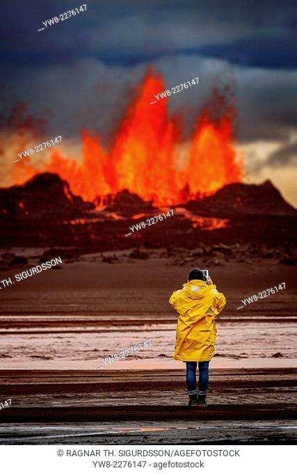 Woman taking pictures with a tablet at the volcano eruption at the Holuhraun fissure, by the Bardarbunga Volcano, Iceland