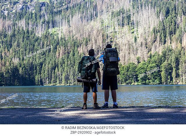 Two hikers on the shore of Black Lake, Sumava, Czech Republic