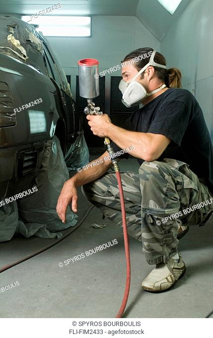 Mechanic in a Body Shop Painting with an Automotive Spray Gun, Laval, Quebec
